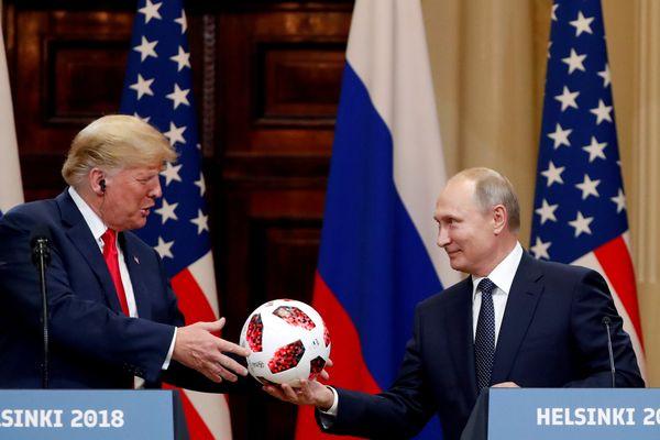 Presiden AS Donald Trump (kiri) menerima bola sepak dari Presiden Rusia Vladimir Putin (kanan) dalam konferensi pers bersama setelah keduanya bertemu membahas sejumlah isu di Helsinki, Finlandia, Senin (16/7). - Reuters/Grigoriy Dukor