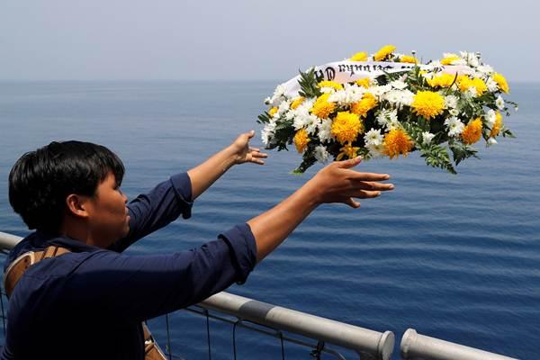 Keluarga korban melemparkan karangan bunga saat prosesi tabur bunga di lokasi jatuhnya pesawat Lion Air JT 610, di perairan Tanjung Karawang, Jawa Barat, Selasa (6/11/2018). - Reuters/Beawiharta