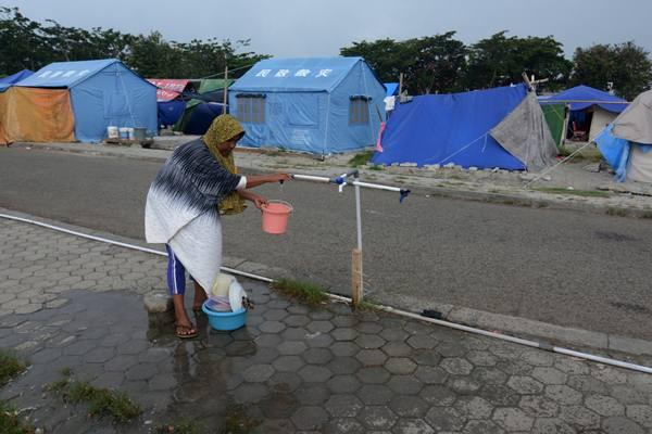 Warga terdampak gempa mencuci peralatan dapur di kamp pengungsian sementara di halaman Masjid Agung Darussalam Palu, Sulawesi Tengah, Kamis (8/11/2018). - Antara