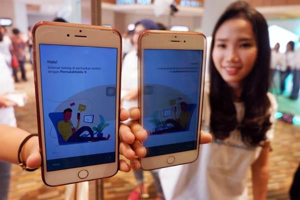 Model memperlihatkan aplikasi mobile banking. - JIBI/Nurul Hidayat