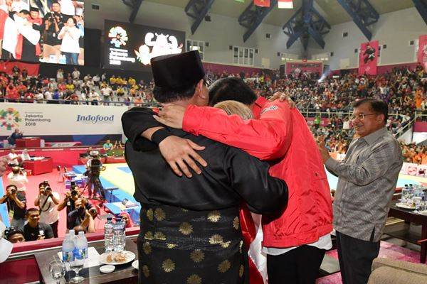 Prabowo Subianto (kiri), atlet pencak silat Indonesia Hanifan Yudani Kusumah, dan Presiden Joko Widodo (kanan) saat final pencak silat Asian Games 2018, Rabu (29/8) di Jakarta. - Dok.Biro Pers Istana