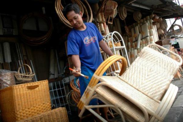 Pengrajin mengecat kursi dari bahan baku rotan di sebuah industri kecil di Pekayon, Bekasi, Jawa Barat, Rabu (10/6/2015). Pengrajin mengaku merasa kesulitan untuk memasarkan hasil kerajinan rotannya dan berharap pemda mendukung usaha mikro kecil menengah tersebut. - Antara