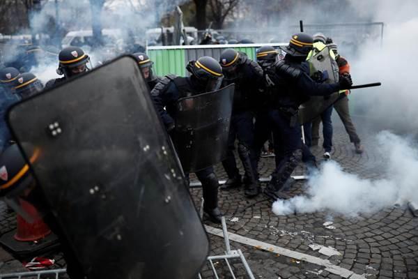 Polisi Prancis melontarkan gas air mata saat menghadapi aksi unjuk rasa memprotest kenaikan harga BBM, di Champs-Elysee, Paris, 24 November 2018. - REUTERS/Benoit Tessier