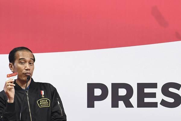 Presiden Joko Widodo menunjukkan kartu Program Keluarga Harapan (PKH) saat sosialisasi kepada penerima dan pendamping di Gelanggang Remaja Jakarta Timur, Jakarta, Senin (3/12/2018). - ANTARA/Puspa Perwitasari