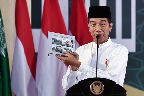 Presiden Joko Widodo menunjukkan buku ketika menghadiri milad satu abad Madrasah Muallimin dan Muallimat Muhammadiyah di Yogyakarta, Kamis (6/12/2018. - ANTARA/Wahyu Putro A