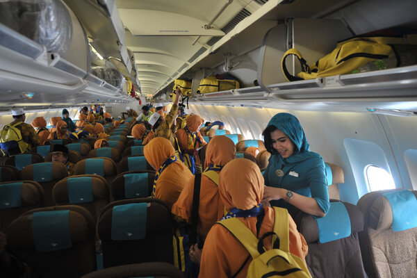 Pramugari Maskapai Garuda Indonesia melayani para jemaah umroh. - Antara/Feny Selly