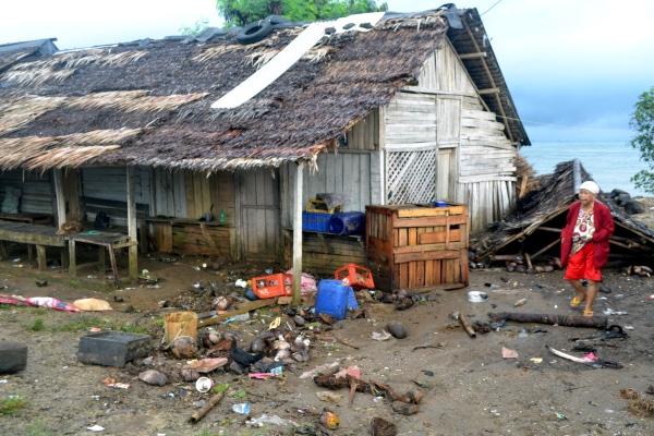 Warga berjalan di samping atap rumah miliknya yang roboh setelah diterjang gelombang tinggi di Kampung Cikadu, Kecamatan Tanjung Lesung, Pandeglang, Minggu (23/12/18). BPBD setempat melaporkan jumlah korban meninggal dunia 13 orang dan ratusan lainya mengalami luka-luka serta 400 lebih rumah warga di pinggir pantai roboh akibat terjangan gelombang pasang dan ombak setinggi hingga 5 meter Sabtu (22/12) malam. - ANTARA FOTO/Muhammad Bagus Khoirunas