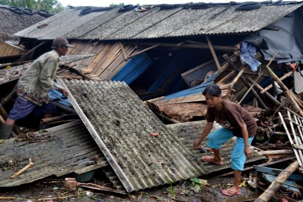 Warga yang rumahnya roboh dihantam tsunami mengambil atap untuk dipasang lagi di Kampung Sinar Laut, Kecamatan Panimbang, Pandeglang, Banten, Minggu (23/12/2018). - ANTARA FOTO/Muhammad Bagus Khoirunas