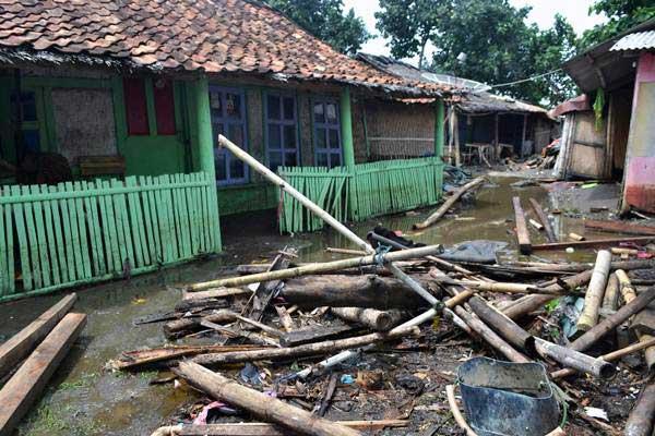 Tumpukan kayu dan bambu yang terhempas gelombang tsunami berserakan di halaman rumah di Kampung Sindangsari, Kecamatan Panimbang, Pandeglang, Banten, Minggu (23/12/2018). - ANTARA/Muhammad Bagus Khoirunas