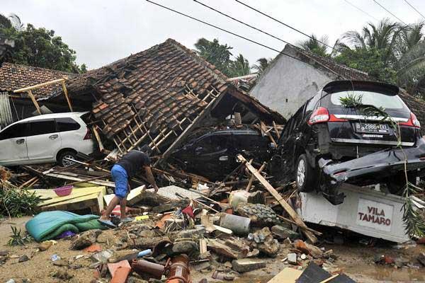 Warga mengais barang di antara reruntuhan villa Tamaro yang porak poranda diterjang tsunami, di Pantai Carita, Pandeglang, Banten, Minggu (23/12/2018). - ANTARA/Asep Fathulrahman