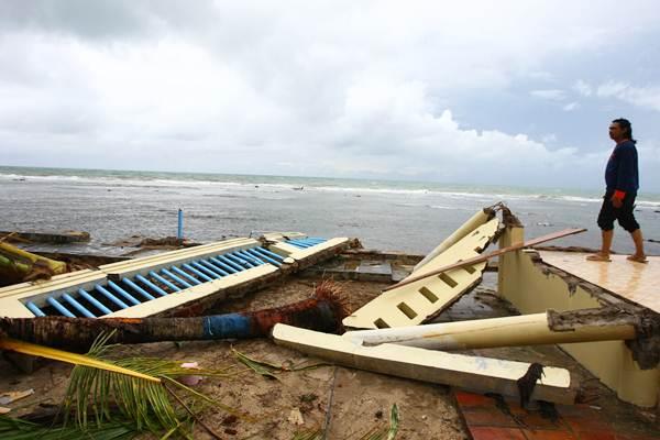 Pengelola berdiri di atas bekas bangunan penginapan yang luluh lantah akibat diterjang tsunami, di kawasan Pantai Carita, Pandeglang, Banten, Selasa (25/12/2018)./ANTARA FOTO - Muhammad Iqbal