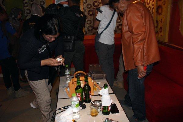 Dua polisi memeriksa barang-barang di meja di dalam ruang nomor 18 di tempat hiburan Gv saat tim gabungan melakukan razia narkoba pada Sabtu (29 - 12) malam. - Bisnis/Tri Rahayu