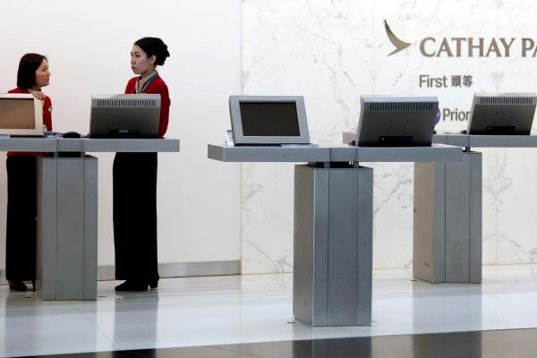 Pegawai Cathay Pacific Airways mengobrol di konter bagi penumpang kelas satu di Bandara Hong Kong, Hong Kong, China, Rabu (4/4/2018). - Reuters/Bobby Yip