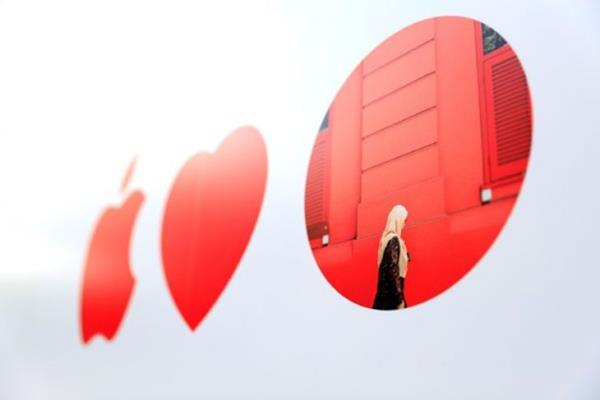 Logo Apple berada di sebelah lambang hati dan titik merah menggambarkan karya seniman lokal di fasad toko Apple Singapura pertama, Jumat (5/5/2017). - Reuters
