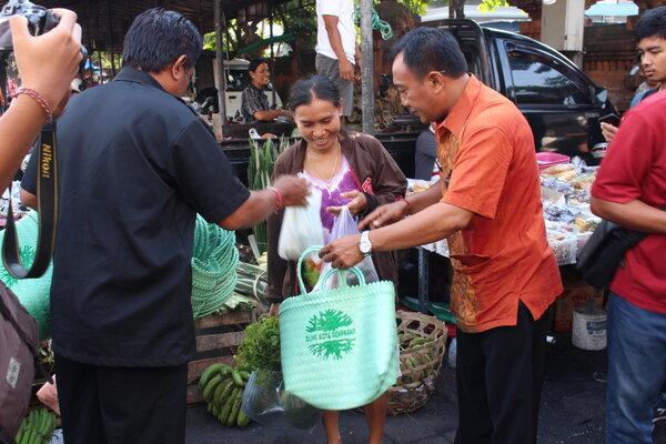 Petugas Dinas Lingkungan Hidup dan Kebersihan Denpasar membagikan kantong belanja ramah lingkungan pengganti kantong plastik pada pemberli di Pasar Kereneng, Selasa (8/1/2019). - Ni Putu Eka Wiratmini