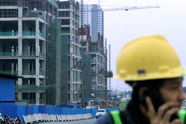 Pekerja beraktivitas di kawasan proyek pembangunan suatu apartemen, Senin (15/10/2018). - ANTARA/Risky Andrianto