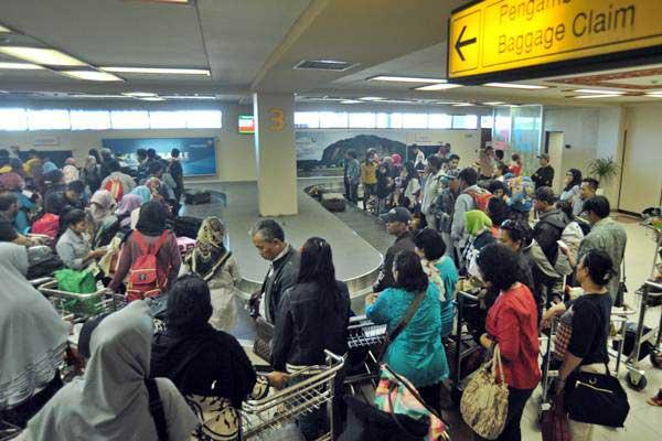Pemudik mengambil bagasi saat tiba di Bandara Internasional Minangkabau (BIM), Padangpariaman, Sumatra Barat, Senin (19/6). - Antara/Iggoy el Fitra
