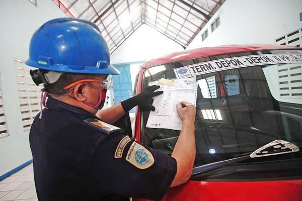 Petugas memeriksa kelayakan kendaraan saat uji kendaraan umum di Tempat Uji KIR, Kali Mulya Depok , Jawa Barat, Senin (7/1/18). - ANTARA/Kahfie kamaru