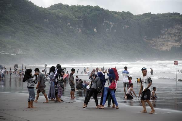 Pengunjung menikmati suasana Pantai Parangtritis, Bantul, DI Yogyakarta, Selasa (25/12/2018). - ANTARA FOTO/Hendra Nurdiyansyah