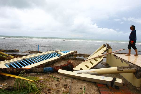 Pengelola berdiri di atas bekas bangunan penginapan yang luluh lantah akibat diterjang tsunami, di Pantai Carita, Pandeglang, Banten, Selasa (25/12/2018). - Antara/Muhammad Iqbal