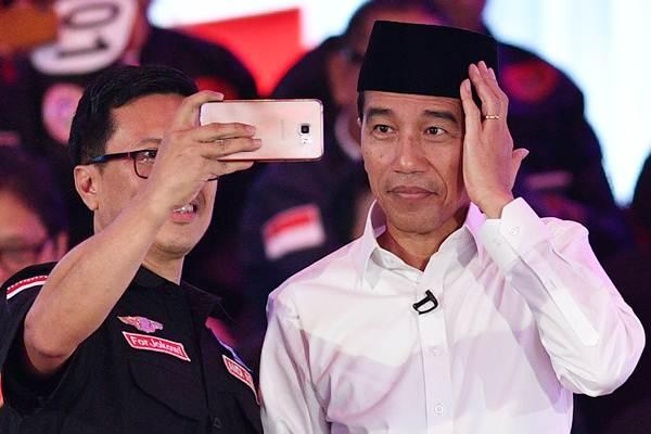 Capres nomor urut 01 Joko Widodo berswafoto dengan pendukungnya saat jeda Debat Pertama Capres & Cawapres 2019, di Hotel Bidakara, Jakarta, Kamis (17/1/2019). - ANTARA/Sigid Kurniawan