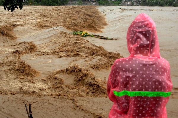 Warga memperhatikan aliran sungai Jeneberang yang meluap di Kabupaten Gowa, Sulawesi Selatan, Selasa (22/1/2019). Meluapnya sungai Jeneberang akibat curah hujan yang tinggi membuat sejumlah daerah di Kabupaten Gowa terendam banjir. - Antara/Abriawan Abhe