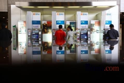 Nasabah BNI sedang menggunakan ATM.