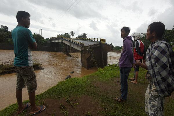 Warga menyaksikan Jembatan Manuju yang ambruk akibat diterjang air di Desa Moncongloe, Manuju, Kabupaten Gowa, Sulawesi Selatan, Rabu (23/1/2019). Jembatan tersebut ambruk karena meluapnya air Sungai Jenneberang akibat tingginya curah hujan. - Antara/Yusran Uccang