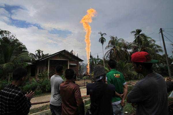 Warga menyaksikan semburan api di lokasi pengeboran minyak illegal yang dikelola warga di kawasan Dusun Kamar Dingin Desa Pasir Putih, Ranto Panjang Peureulak, Kabupaten Aceh Timur, Aceh, Rabu (25/4/2018). - ANTARA/Rahmad