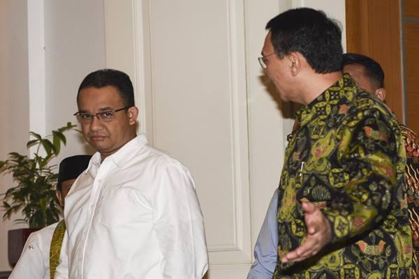 Basuki Tjahaja Purnama atau Ahok (kanan) dan Anies Baswedan (kiri) berjalan bersama usai melakukan pertemuan di Balai Kota, Jakarta, Kamis (20/4). - Antara