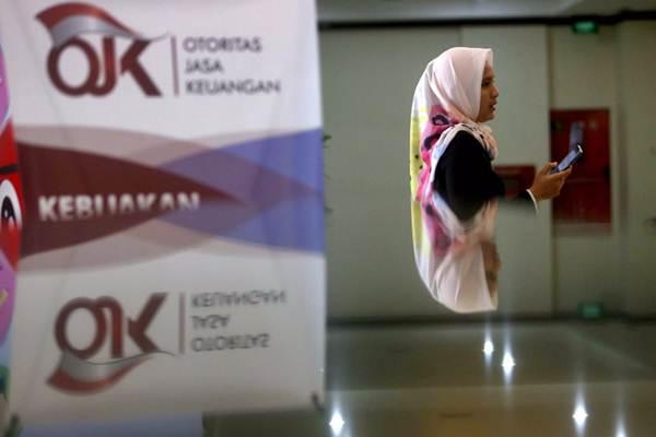 Karyawan melintas di dekat logo Otoritas Jasa Keuangan (OJK) di Jakarta, Rabu (3/10/2018). - Bisnis - Nurul Hidayat