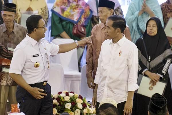 Presiden Joko Widodo (kedua kanan) berbincang dengan Gubernur DKI Jakarta Anies Baswedan (kiri) usai menyerahkan Sertifikat Tanah untuk Rakyat di Cengkareng, Jakarta, Rabu (9/1/2019). - ANTARA/Puspa Perwitasari