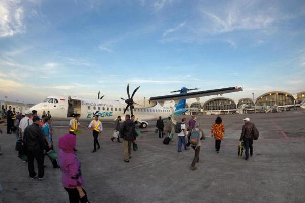 Penumpang pesawat udara Garuda Indonesia berjalan menuju pesawat di Bandara Sultan Hasanuddin Makassar, Sulawesi Selatan, Senin (1/9/2014) untuk terbang dengan rute MakassarBau-Bau. - Bisnis/Paulus Tandi Bone