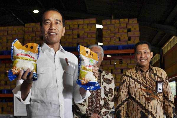 Presiden Joko Widodo (kiri) didampingi Kepala Bulog Budi Waseso (kanan) menunjukkan beras kemasan Bulog saat mengecek stok beras di Kompleks Pergudangan Bulog, Jakarta, Kamis (10/1/2019). - ANTARA/Puspa Perwitasari