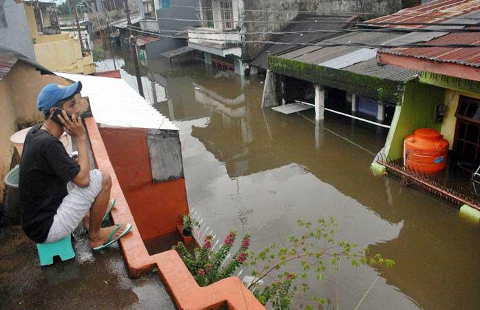 Warga menelpon di atas rumahnya saat banjir di Kecamatan Manggala, Makassar, Sulawesi Selatan, Rabu (23/1/2019). Akibat diguyur hujan dalam beberapa hari sejumlah daerah di Makassar terendam banjir. - ANTARA/Abriawan Abhe
