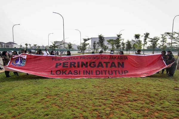Sejumlah petugas Satuan Polisi Pamong Praja (Satpol PP) membentangkan spanduk penyegelan di Pulau D Reklamasi Teluk Jakarta, Jakarta, Kamis (7/6/2018). - ANTARA/Dhemas Reviyanto