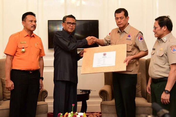 Kepala BNPB, Letjen Doni Monardo (dua dari kanan) secara simbolis menyerahkan bantuan di kantor Gubernur Sulsel, Kamis (24/1 - 2019).
