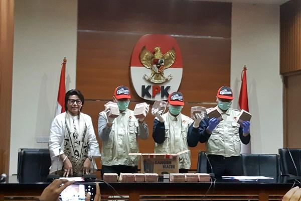 Wakil Ketua KPK Basaria Pandjaitan (kiri) menujukkan bukti uang tunai hasil OTT yang diduga sebagai suap atas proyek proyek infrastruktur di Kabupaten Mesuji, Lampung, Tahun Anggaran 2018, dalam konferensi pers di Gedung KPK, Kamis (24/1/2019). (Ilham Budiman - Bisnis).