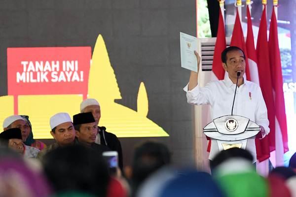 Presiden Joko Widodo memperlihatkan sertifikat ketika memberikan sambutan saat penyerahan sertifikat tanah untuk rakyat di Cigombong Sukabumi, Jawa Barat, Rabu (26/12/2018). - ANTARA FOTO/Wahyu Putro A