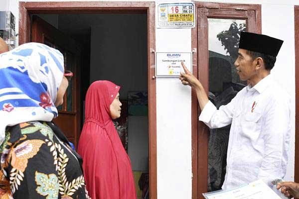Presiden Joko Widodo (kanan) meninjau rumah yang telah dipasang listrik gratis untuk keluarga prasejahtera, di Kampung Pasar Kolot, Garut, Jawa Barat, Jumat (18/1/2019). - ANTARA/Puspa Perwitasari