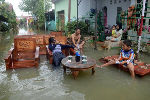Warga beristirahat saat membersihkan perabot yang terendam banjir di Perumahan BTN Kodam 3, Makassar, Sulawesi Selatan, Jumat (25/01/2019). Banjir di kawasan itu berangsur surut, warga mulai kembali ke rumahnya untuk membenahi dan membersihkan perabot yang terendam banjir. - Antara/Sahrul Manda Tikupadang