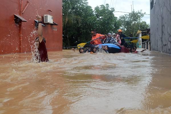 Tim relawan mengevakuasi warga yang terjebak banjir di Perumahan Bung Permai, Makassar, Sulawesi Selatan, Rabu (23/1/2019). Ketinggian banjir di kawasan tersebut mencapai satu meter akibat meluapnya Sungai Tello. - Antara