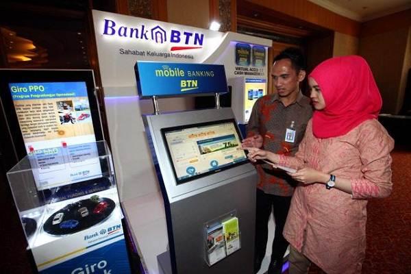 Pengunjung mencari informasi mengenai Bank BTN di sebuah pameran.  -  Bisnis/Dwi Prasetya
