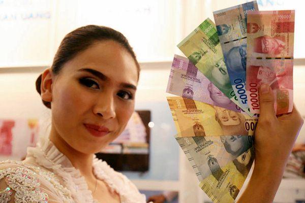 Model memegang uang rupiah kertas, - JIBI/Nurul Hidayat