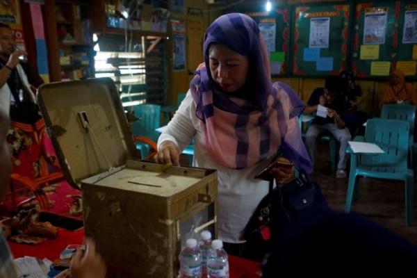 Seorang penduduk memberi suara dalam referendum di Filipina pada Senin, (21/1/2019) - Reuters/Marconi B. Navales