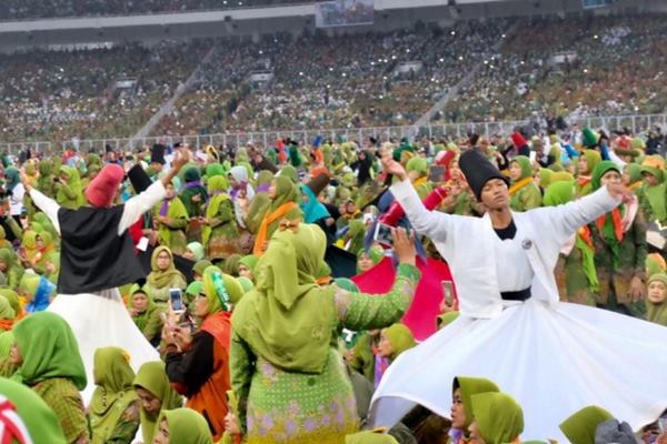Ibu-ibu Muslimat NU tetap berada di tengah stadion Gelora Bung Karno Jakarta, meski hujan deras mengguyur, dalam rangka merayakan Hari Lahir (Harlah) Muslimat Nahdlatul Ulama ke-73, pada Minggu (27/1). Tak hanya para ibu, 999 penari sufi dari Pondok Pesantren Sabilil Muttaqin, Takeran, Magetan, Jawa Timur tetap bertahan di tengah guyuran hujan yang cukup deras di Stadion Utama Gelora Bung Karno, Jakarta.(antara - Aubrey Kandelila Fanani)