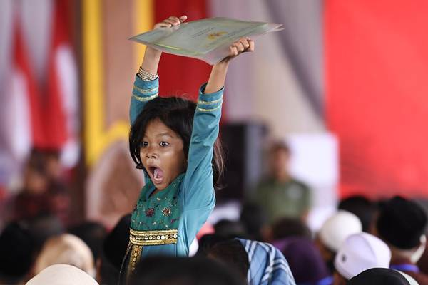 Seorang anak mengangkat sertifikat tanah saat berlangsung Penyerahan Sertifikat Tanah untuk Rakyat oleh Presiden Joko Widodo di Bangkalan, Madura, Jawa Timur, Rabu (19/12/2018). - ANTARA/Puspa Perwitasari