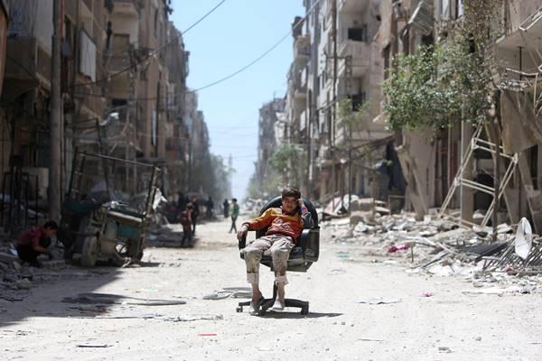 Seorang anak laki-laki duduk di kursi di sepanjang jalan yang rusak di kota Douma di Damaskus, Suriah pada 16 April 2018. - Reuters