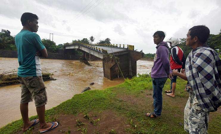 Warga mengamati Jembatan Manuju yang ambruk akibat diterjang air Sungai Jenneberang, di Desa Moncongloe, Manuju, Kabupaten Gowa, Sulawesi Selatan, Rabu (23/1/2019). - ANTARA/Yusran Uccang