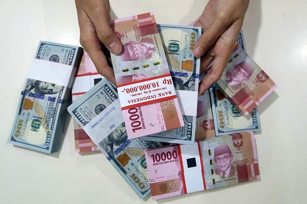 Karyawan menghitung mata uang rupiah dan dolar AS di Jakarta, Senin (1/7/2019). - Bisnis/Abdullah Azzam